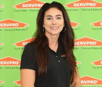 female employee sitting in front of SERVPRO backdrop