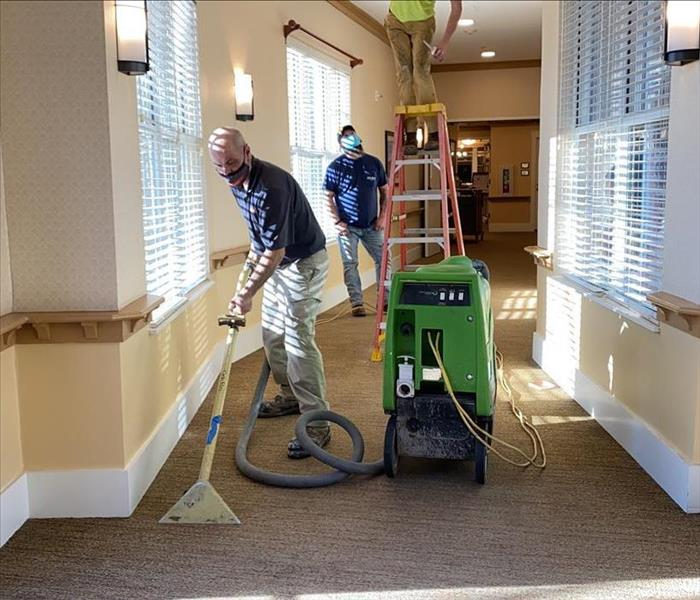 SERVPRO team members are removing water from a carpet.