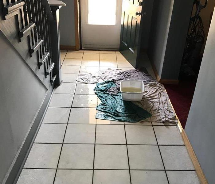 bucket of water on tile floor with wet towels and visible water surrounding the area