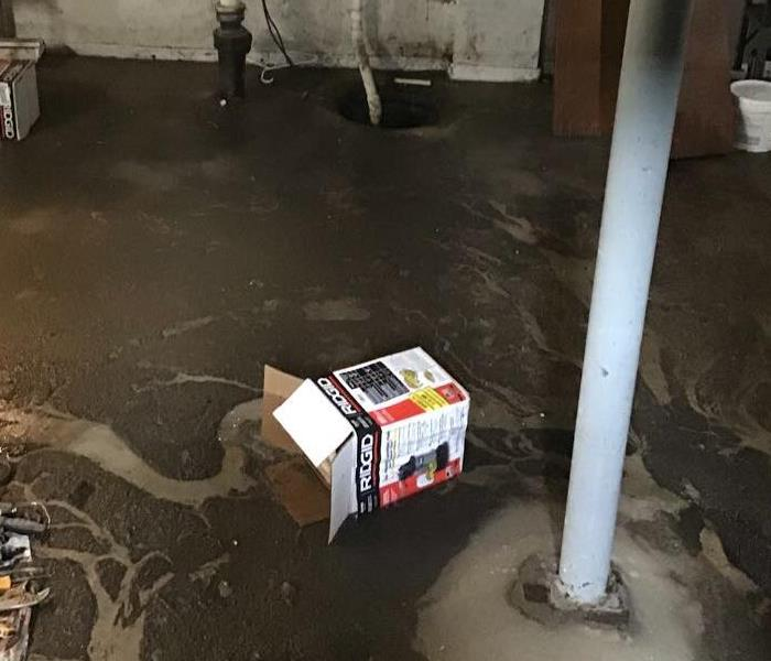 concrete basement floor with layers of sewage on the ground