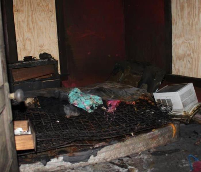 soot and smoke damaged matress, ac unit, and clothing in a boarded up bedroom