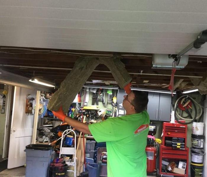 servpro employee ripping drywall out the ceiling of a garage