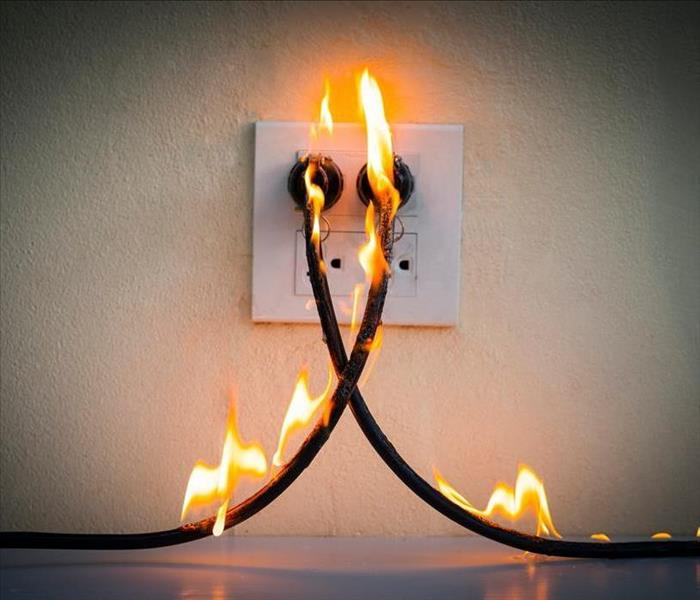 image of electrical chord causing a small fire that has potential to grow rapidly