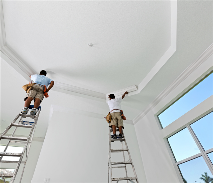Picture is of two men on ladders painting a commercial ceiling white.