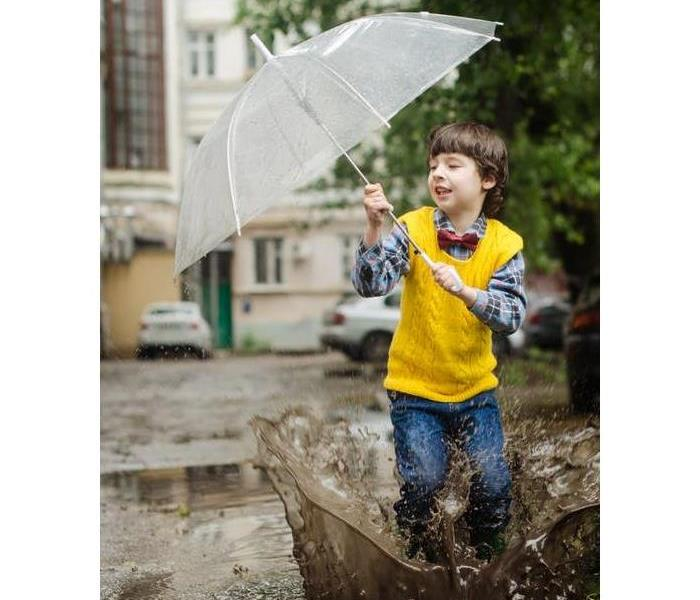 child boy jumping through a rain puddle with an umbrella extended