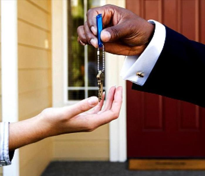 image of landlord handing over keys to a home to tenants