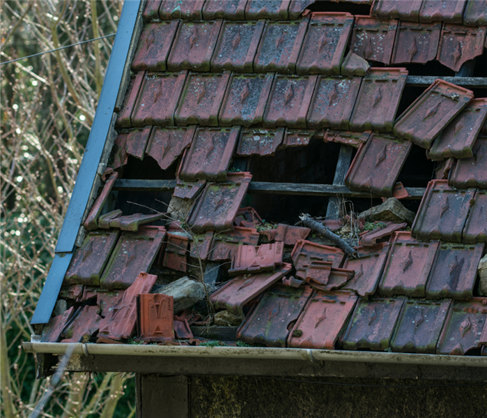 Picture is of a shaker shingle roof that has been ripped all apart due to high winds