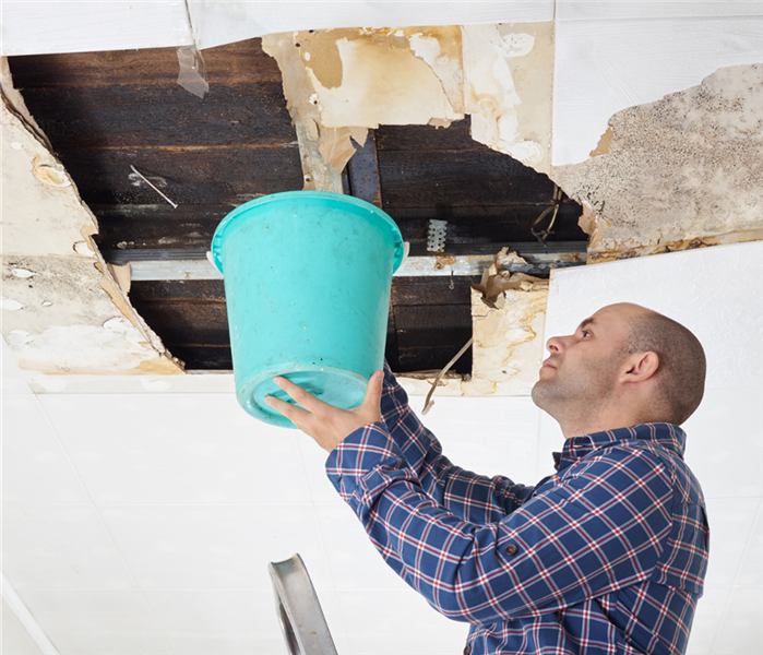Picture is of a man holding a bucket to catch water coming out of a commercial paneled roof