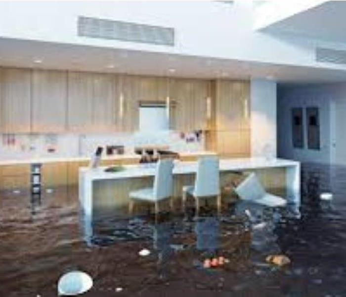 kitchen table under three feet of water with debris floating around