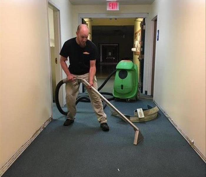 employee in a commercial building hallway holding an extractor